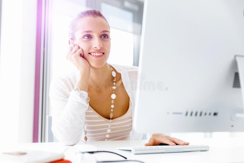 sittande arbetare för attraktivt skrivbordkontor royaltyfri bild