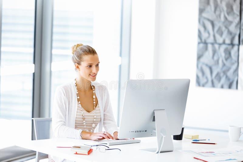 sittande arbetare för attraktivt skrivbordkontor arkivfoto