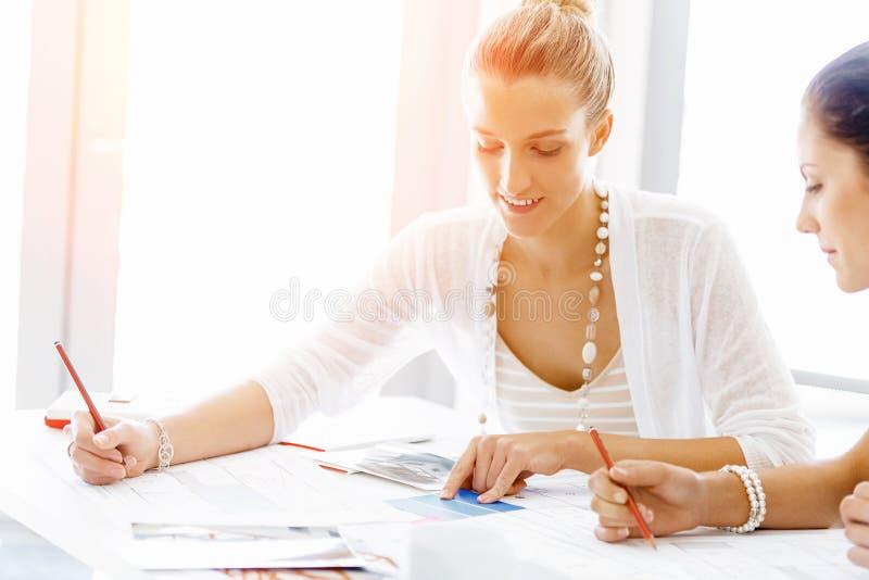 sittande arbetare för attraktivt skrivbordkontor royaltyfria foton