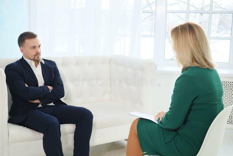 Sittande armar för ung affärsman som korsas på soffan som talar till hans terapeut royaltyfri bild