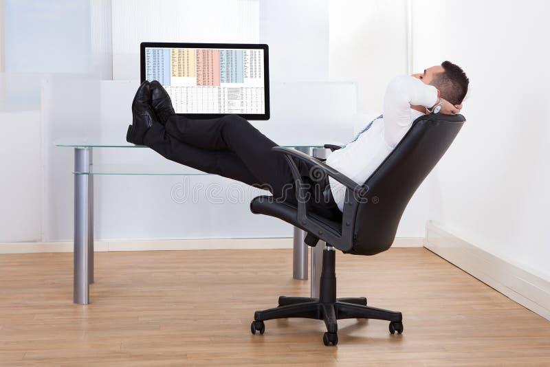 Sittande fot för avkopplad affärsman upp på skrivbordet royaltyfri fotografi