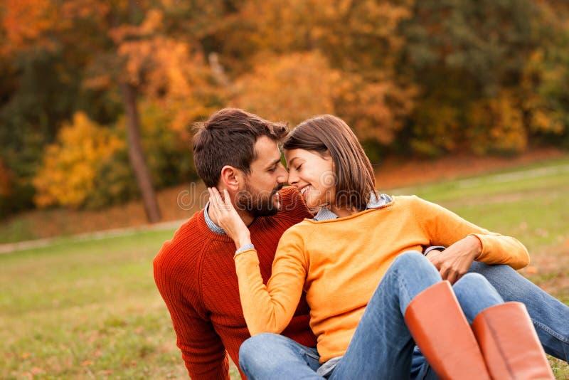 Sittande framsida för härliga unga par - till - framsida och le arkivfoto