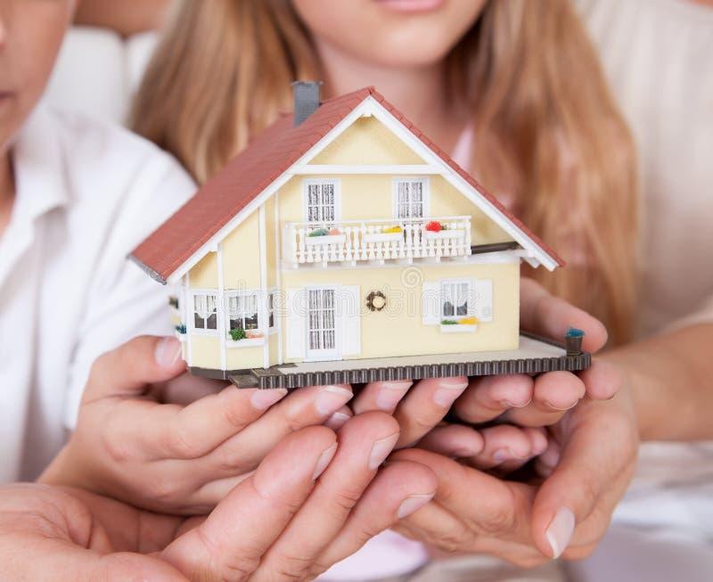 Sittande Holdingminiatyrmodell för familj av huset royaltyfri foto