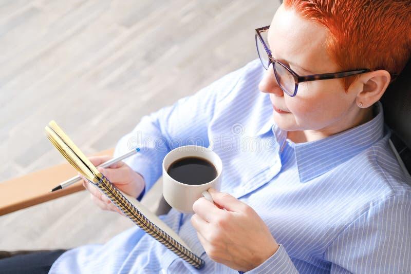 sittande kvinna för affärsstol Attraktiv ung affärskvinna som sitter i en stol som ser dokument Drinkkaffe fotografering för bildbyråer