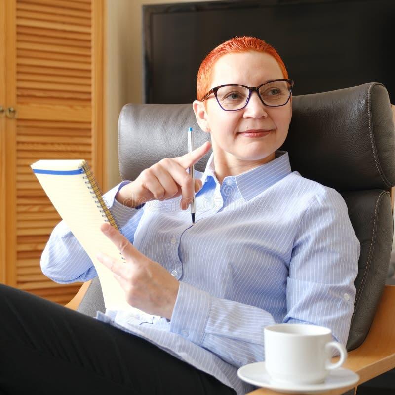 sittande kvinna för affärsstol Attraktiv ung affärskvinna som sitter i en stol som ser dokument Drinkkaffe arkivfoto