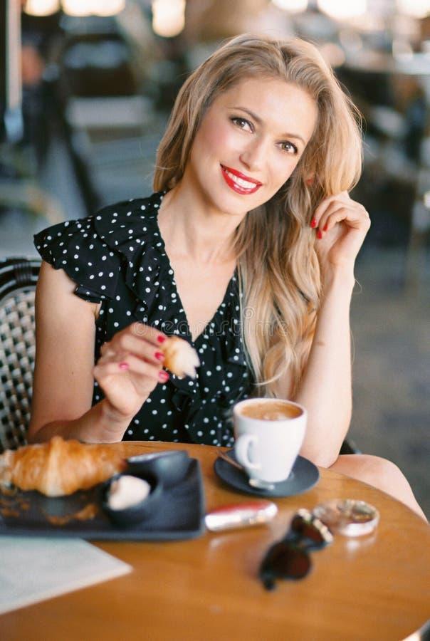 sittande kvinna f?r h?rlig cafe arkivfoton