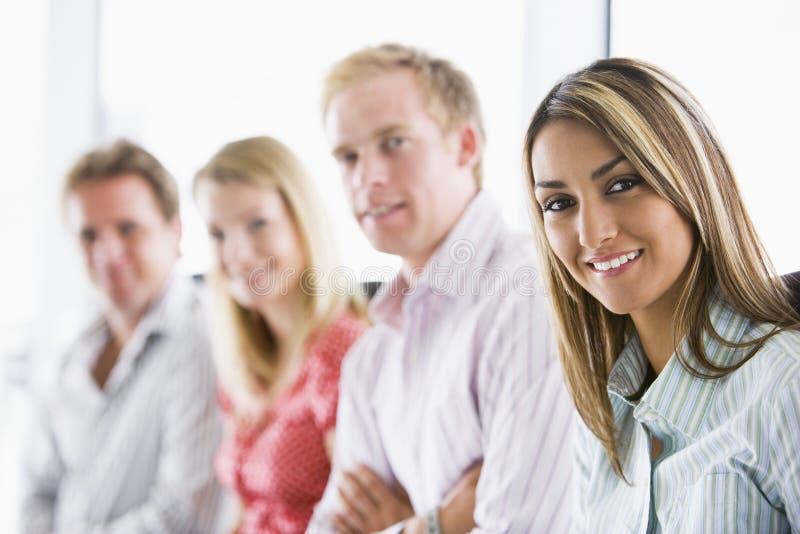 sittande le för businesspeople fyra inomhus arkivbild