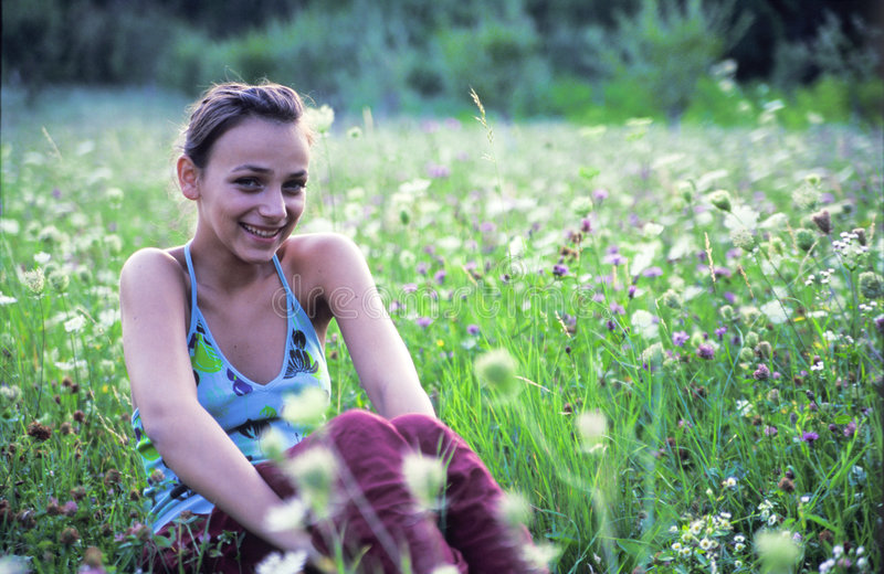 sittande le för flickagräs fotografering för bildbyråer