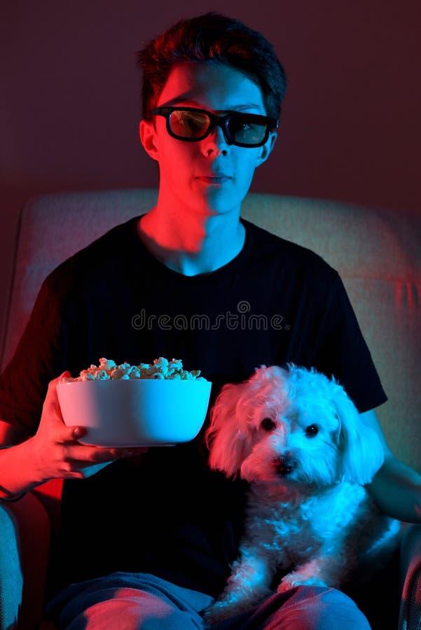 Sittande och hållande ögonen på film för pojke arkivfoto