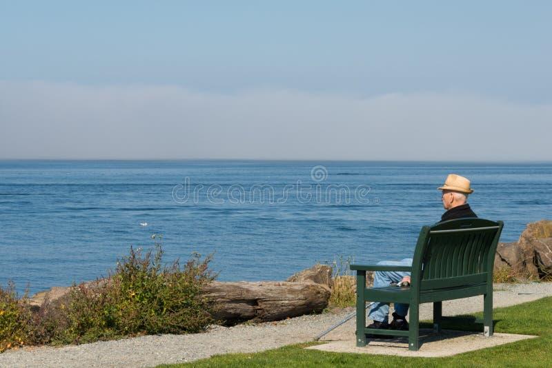 Sittande se för äldre man ut till havet royaltyfria foton