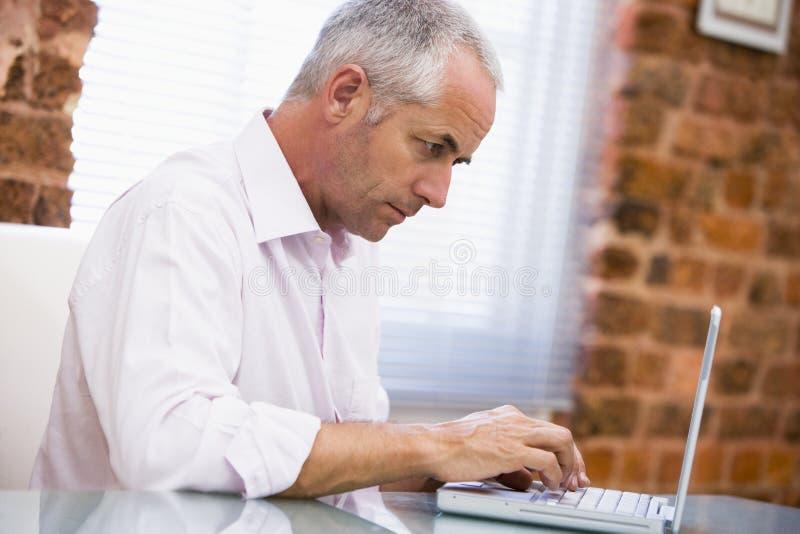 sittande skrivande för affärsmanbärbar datorkontor arkivfoto