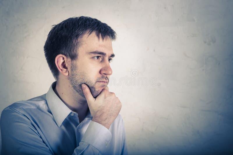 Sittande skulle tänka för ung caucasian man och att se upp, förväxlat om en idé, försöka att finna en lösning arkivfoton