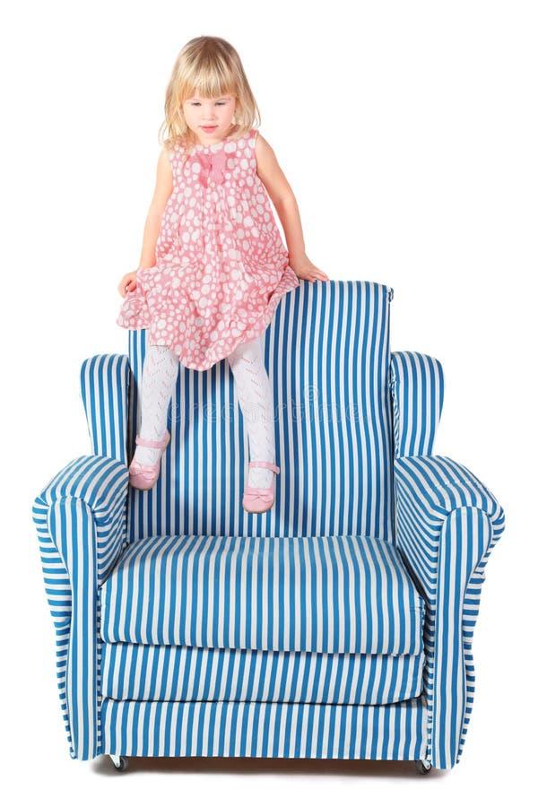 sittande slitage för tillbaka stolsklänningflicka arkivfoto