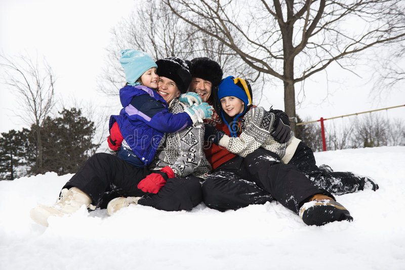 sittande snow för familj royaltyfri fotografi
