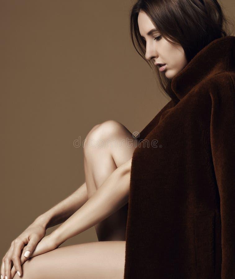Sittande tänka för ung härlig hipsterflicka som är sexigt i det bruna våromslaget som är naket på beiga royaltyfria foton