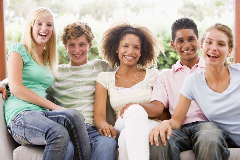 sittande tonåringar för soffagrupp royaltyfri bild