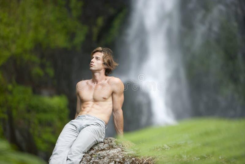 sittande vattenfall för man royaltyfri foto