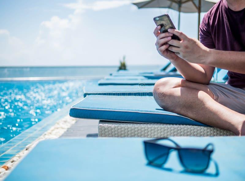 Sittande vila för ung man och använda den smarta telefonen på simbassängen Baner för design för begrepp för resande för sommarfer royaltyfri fotografi