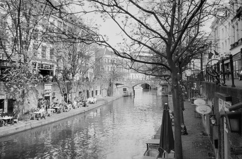 Sittande yttersida för folk längs en kanal i Utrecht, Holland arkivbild