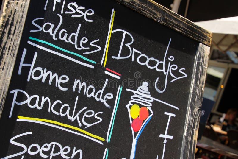 SITTARD, PAÍSES BAJOS - JUIN 29 2019: Ciérrese para arriba de menú escrito mano en el tablero de tiza negro de restaurante del du foto de archivo