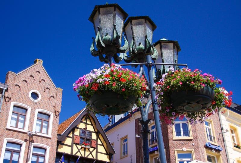 SITTARD SOM ÄR NEDERLÄNDSK - JUIN 29 2019: Sikt för låg vinkel på gatalampor som dekoreras med blommakorgar mot blå himmel med me royaltyfria bilder
