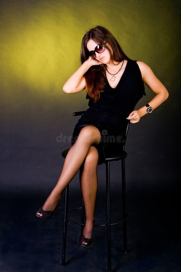 Sitted Dame auf schwarzem Kleid lizenzfreie stockfotografie