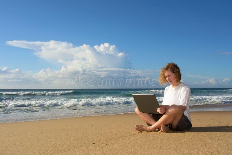 sitter den blonda affärskvinnaanteckningsboken för stranden royaltyfria bilder