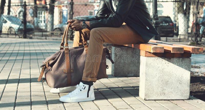 Sitter den eleganta afrikanska mannen för mode med påsen på bänken royaltyfri foto