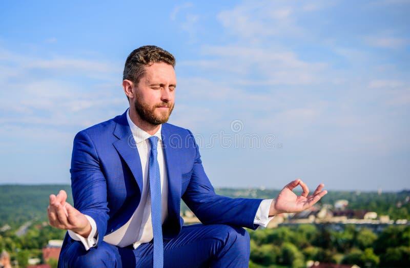 Sitter den formella dräkten för affärsmannen lotusblomma poserar och meditera utomhus Entreprenörfyndminut som ska kopplas av och royaltyfri foto