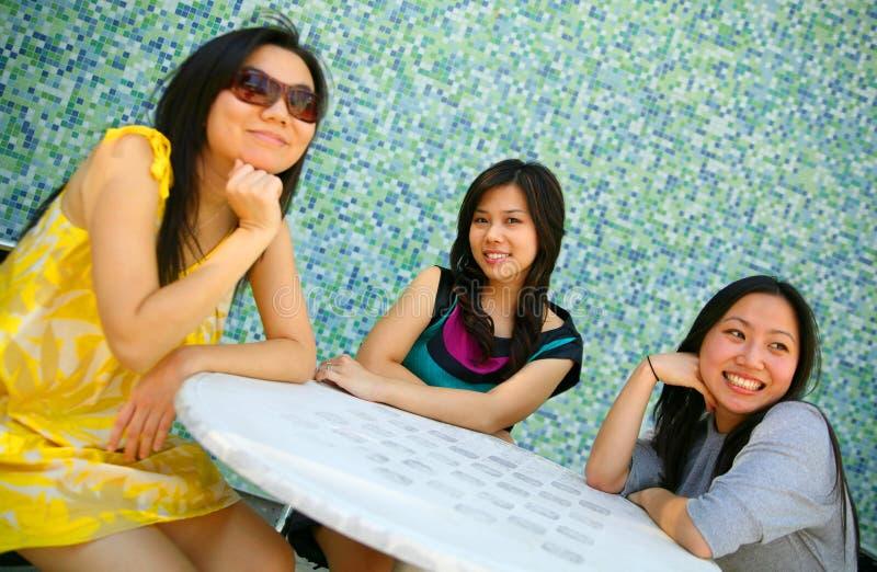 sitter den lyckliga utomhus- inställningen för den asiatiska flickan tre arkivbild