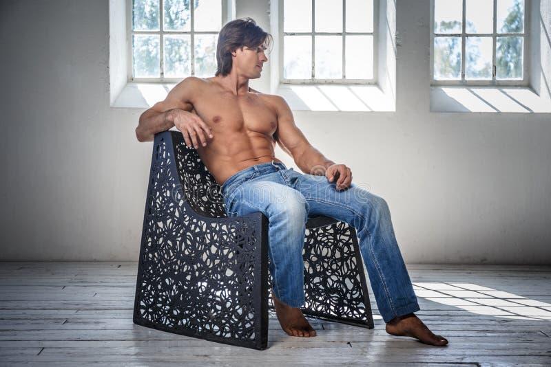 Sitter den manliga modellen för Shirtless kondition i jeans på en stol royaltyfria foton