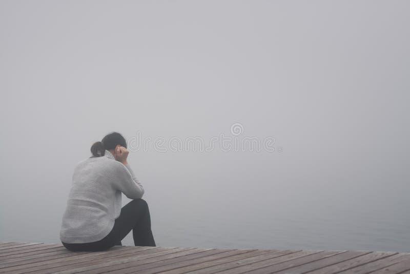 Sitter den unga kvinnan för förtvivlan ensamt på kanten av en träbana av en broböjelse och SAD borttappat i tanke i dimman royaltyfri foto
