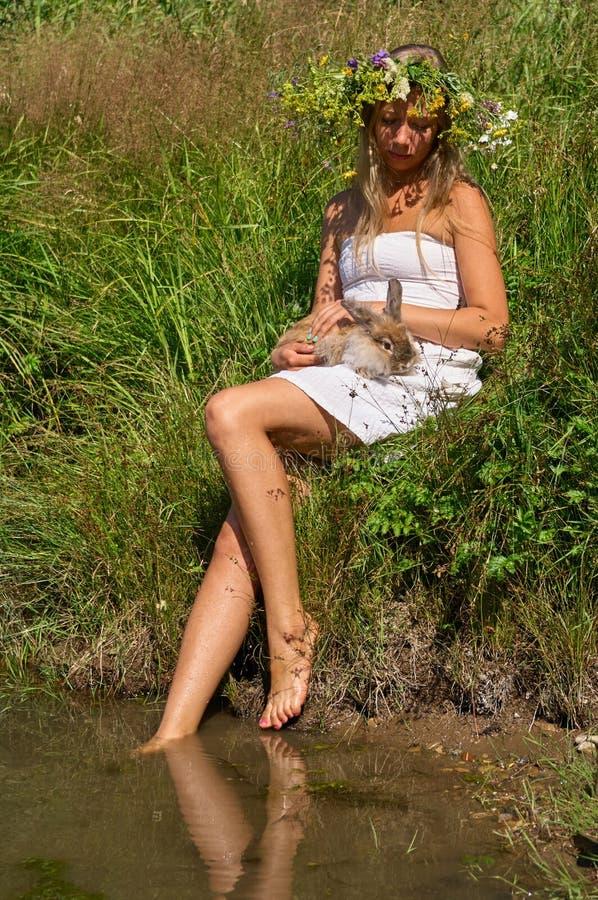 Sitter den unga kvinnan för den nätta flickan med naturligt blont långt hår och den härliga framsidan i den vita klänning- och bl arkivfoton