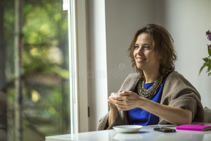 sitter framme av fönstret med en kopp te glädje arkivbild