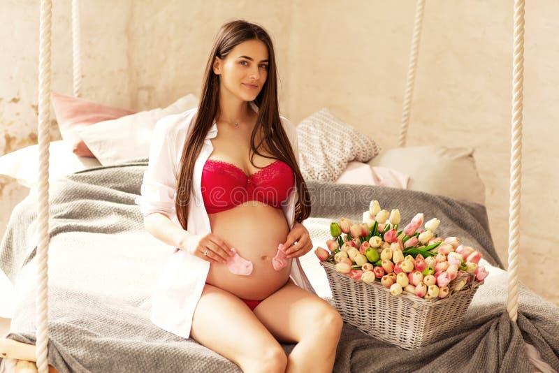 Sitter gravida härliga ställningar för en flicka i ett rum av ljus - rosa färg till fotografering för bildbyråer