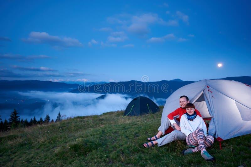 Sitter le person två i ett tält på gryning royaltyfri fotografi
