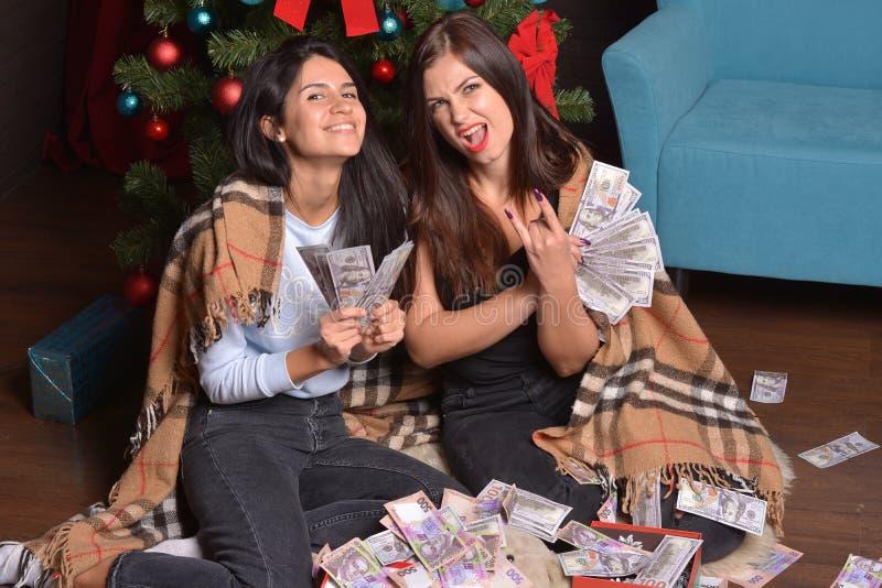 Sitter lycklig kvinna två under en julgran på golvet som beströs med pengar fotografering för bildbyråer