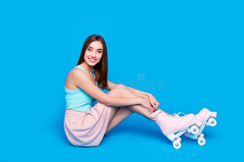 Sitter roligt härligt för fullt för längdsidoprofil för kropp foto för format golvet henne hennes rullar för damhandbandet som be royaltyfria foton