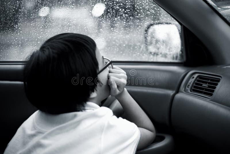 Sitter ser den asiatiska flickan för den monokromma ståenden i bilen och ut ur fönster som håller ögonen på regnet och små droppa royaltyfria bilder