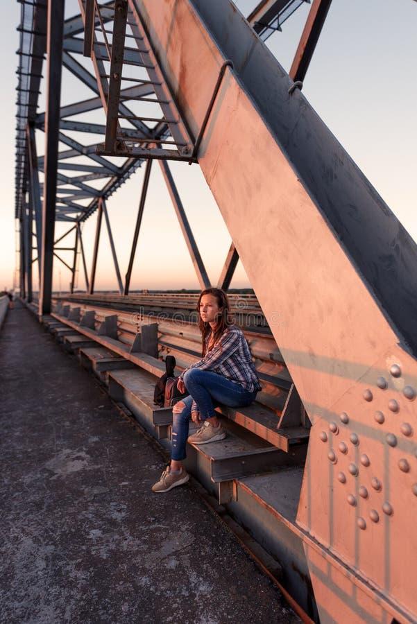 Sitter upproriskt ensamt för tonårig flicka pensively på balustraden av stålbrokonstruktion i övergav skeppsdockor i solnedgångti royaltyfria bilder