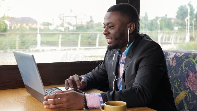 Sitter video pratstund för afro- amerikanska svart mansamtal på datoren i skalm i kafé royaltyfria foton