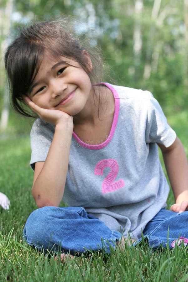 Sittin d'enfant sur penser d'herbe image libre de droits