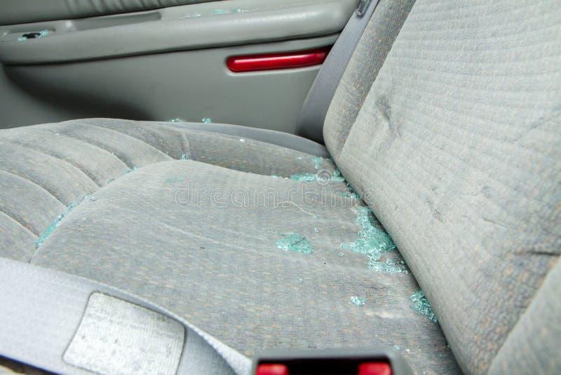 Sittin de vidro quebrado em um assento de um carro imagens de stock