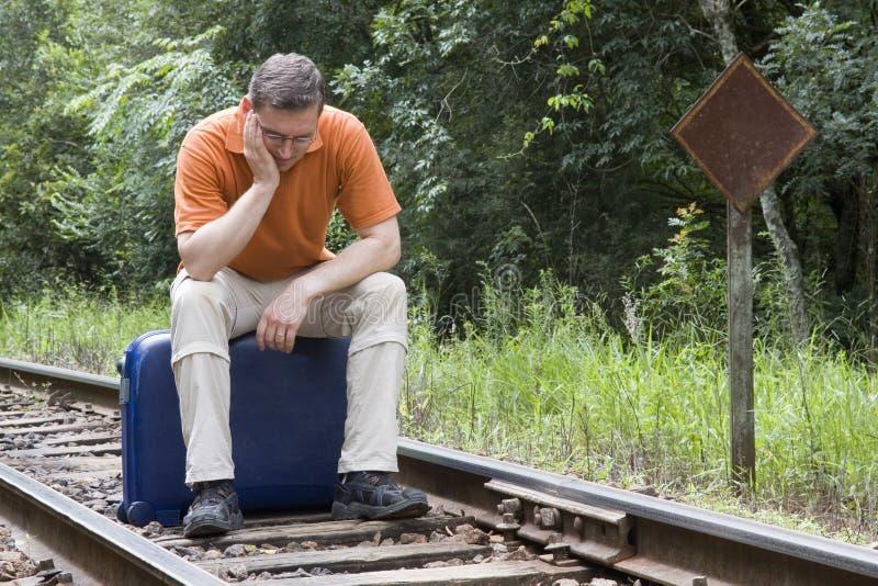 Sittin del hombre en la maleta en pista de ferrocarril foto de archivo libre de regalías