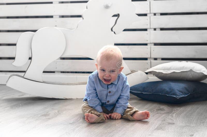 Sittin del ragazzo del piagnucolone sul pavimento Bambino che grida e che grida fotografia stock