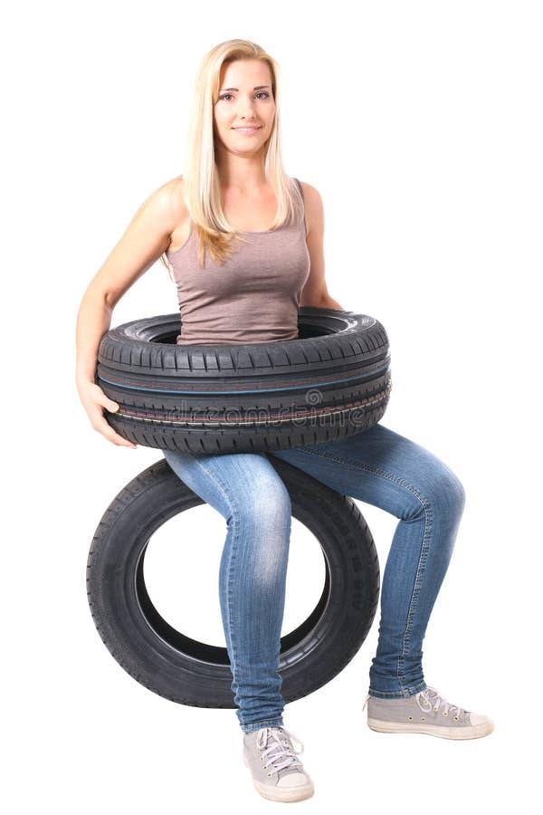 Sittin louro da menina em um pneumático No branco fotos de stock