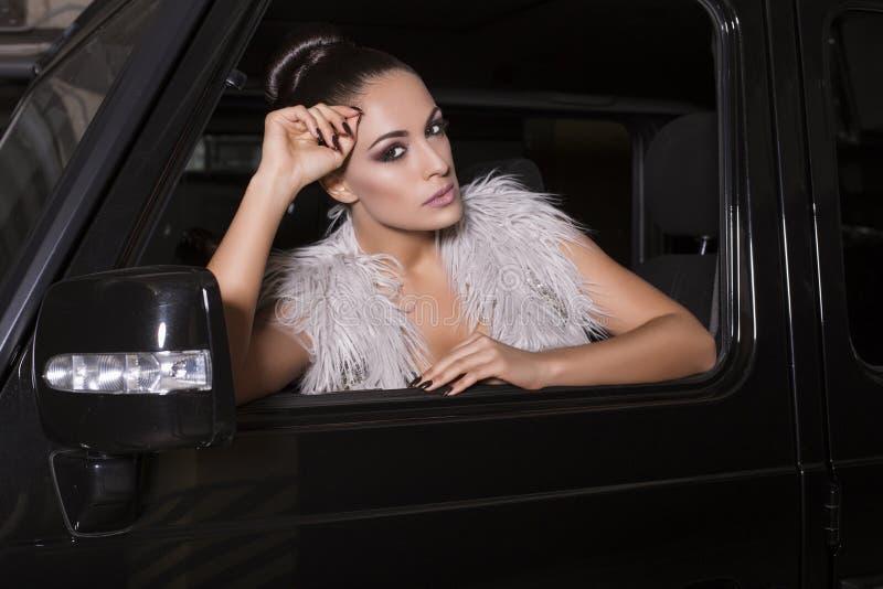 Sittin 'sexy' do motorista da mulher do encanto no carro fotos de stock