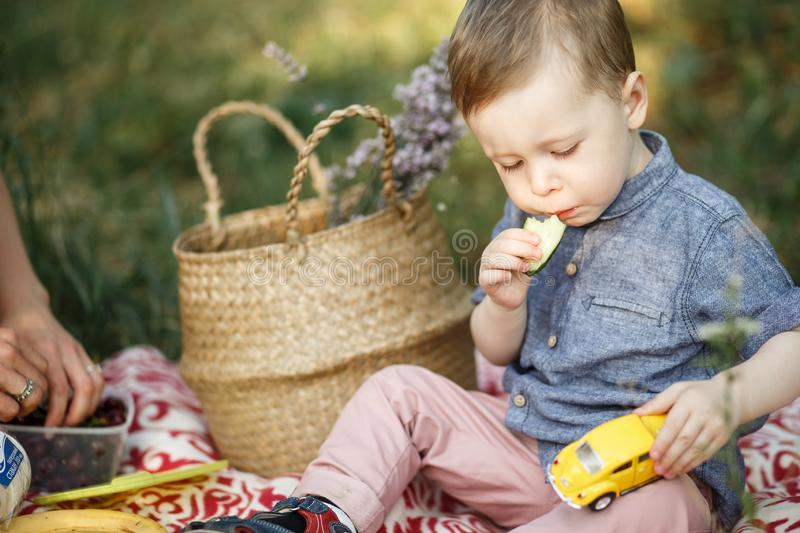 By is sitting on blanket and playing with toy. He has yellow car on his nap. Also kid is eating royalty free stock photos