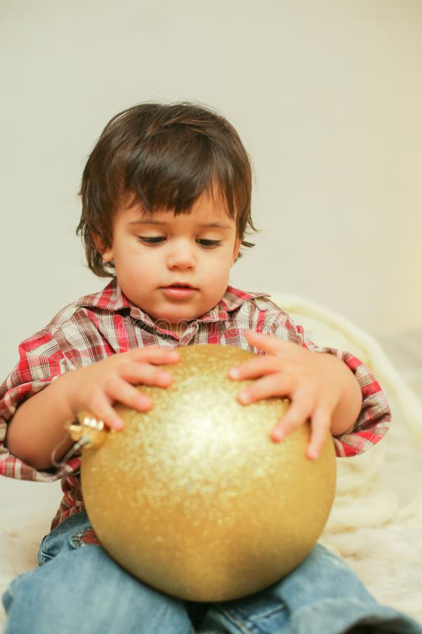 Sitting boy with Christmas ball royalty free stock photos