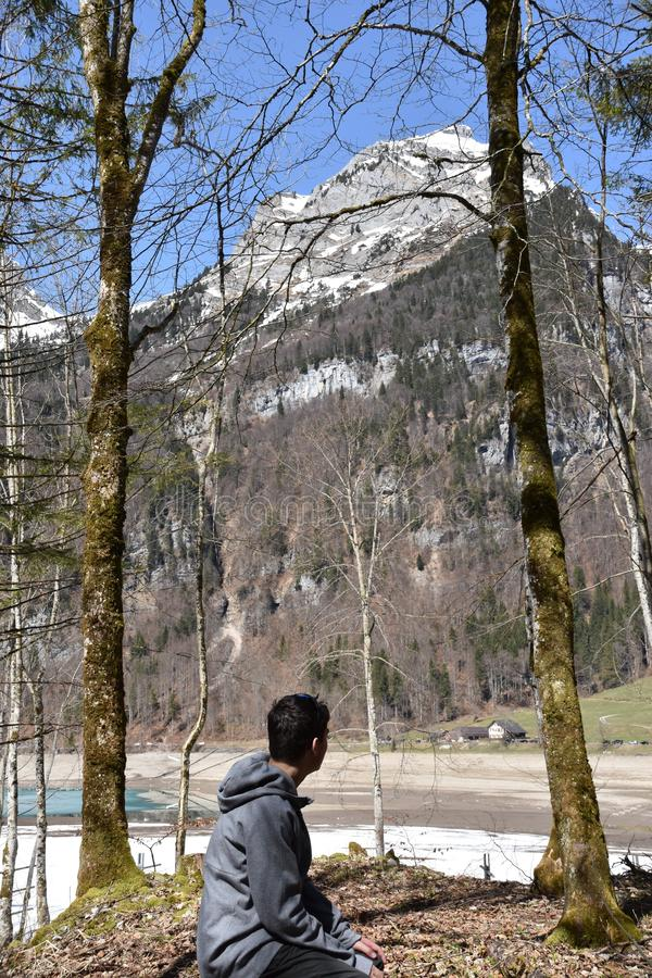 A sitting boy between conifer trees observing Klöntalersee lake in early spring sunny day in Klöntal. Schwyz Alps, kanton Glarus, Switzerland .  On the royalty free stock images